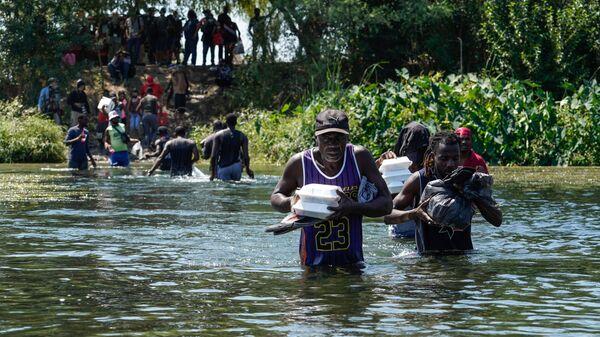 Мигранты из Гаити пересекают границу США и Мексики на реке Рио-Гранде - Sputnik International