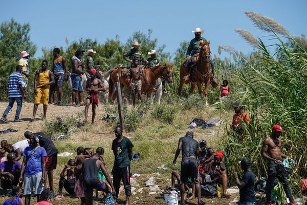 Mounted United States Border Patrol agents look on as Haitian migrants sit on the river bank near an encampment on the banks of the Rio Grande near the Acuna Del Rio International Bridge in Del Rio, Texas on 19 September 2021.  - Sputnik International