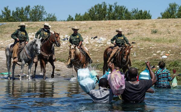 United States Border Patrol agents on horseback try to stop Haitian migrants from entering an encampment on the banks of the Rio Grande near the Acuna Del Rio International Bridge in Del Rio, Texas on 19 September 2021.  - Sputnik International