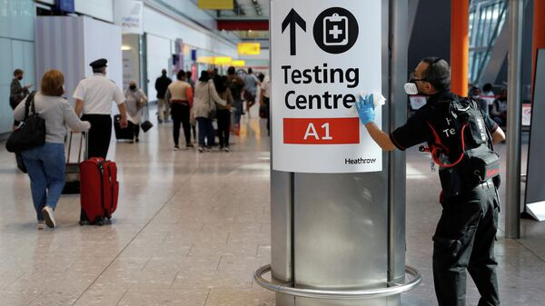 A worker sanitises a sign at the International arrivals area of Terminal 5 in London's  Heathrow Airport, Britain, August 2, 2021 - Sputnik International