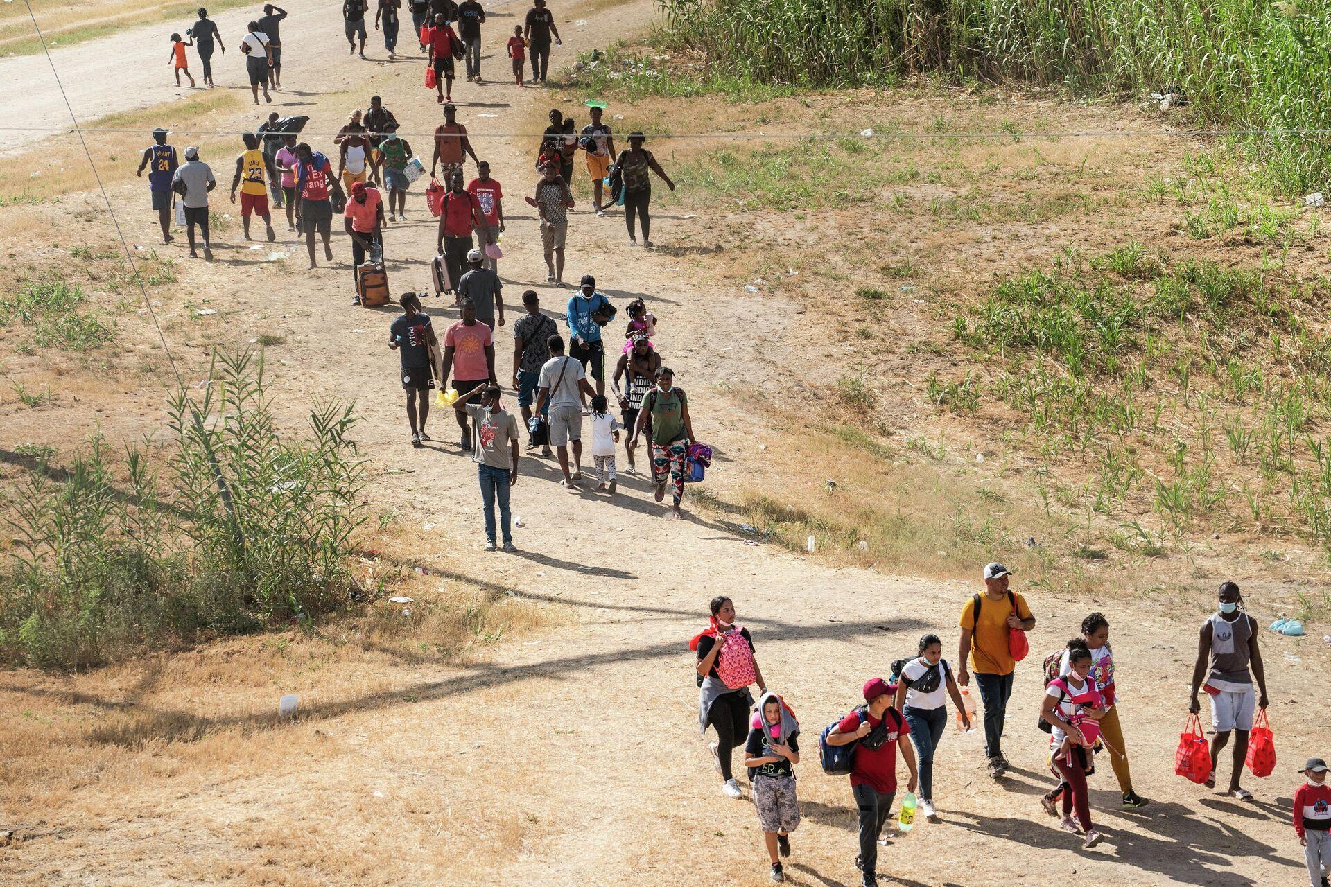 Asylum-seeking migrants walk near the International Bridge between Mexico and the US where asylum-seeking migrants are waiting to be processed in Del Rio, Texas, US, September 15, 2021 - Sputnik International, 1920, 25.09.2021