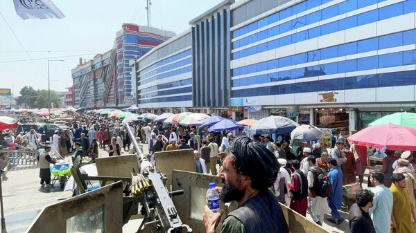 Members of Taliban security forces stand guard as crowds of people walk past in front of a money exchange market in Kabul, Afghanistan September 4, 2021 - Sputnik International
