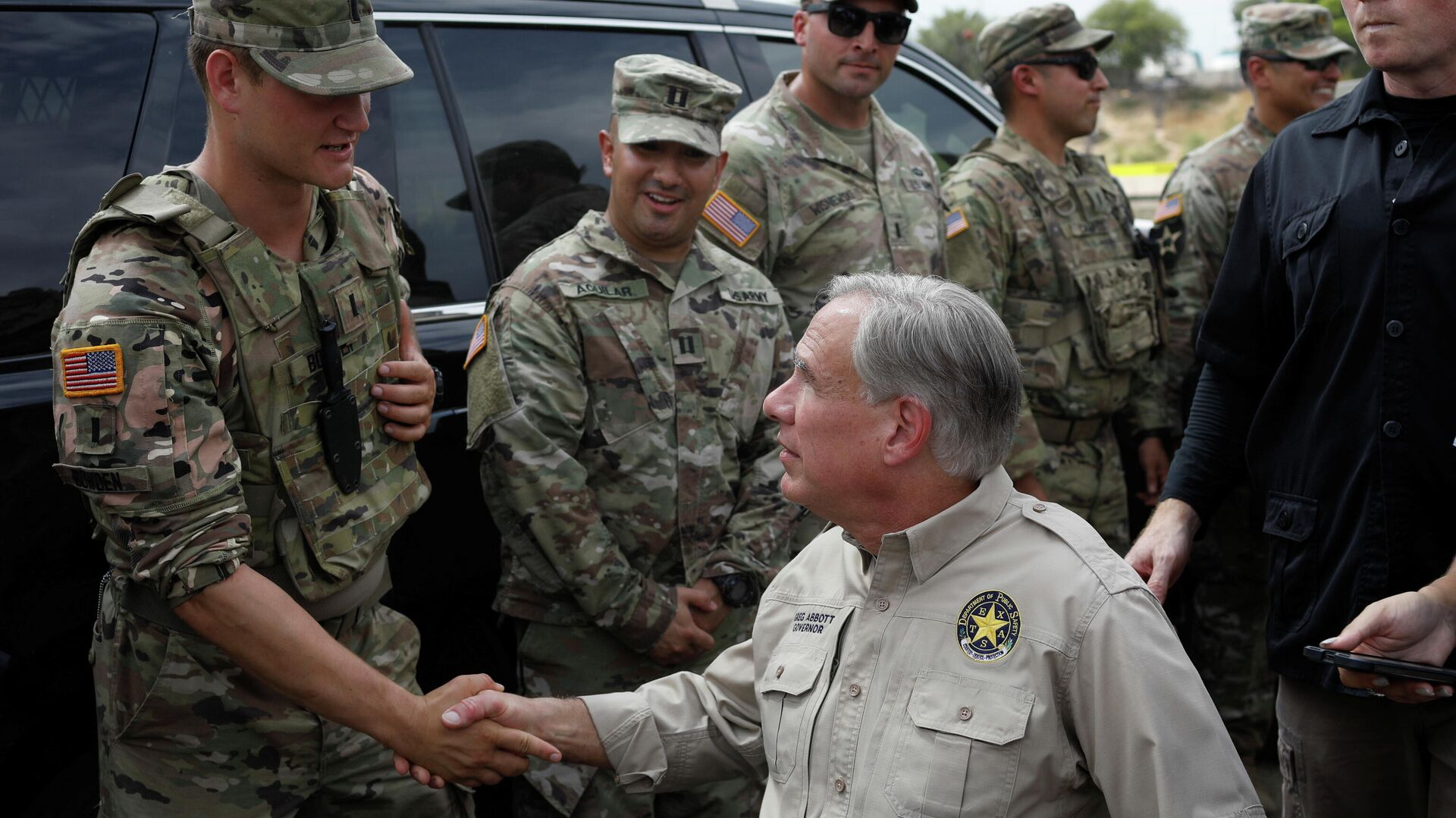 Texas Governor Gregg Abbott shakes hands with a U.S. Soldier after a news conference near the International Bridge between Mexico and the U.S., where migrants seeking asylum in the U.S. are waiting to be processed, in Del Rio, Texas, U.S., September 21, 2021 - Sputnik International, 1920, 23.09.2021