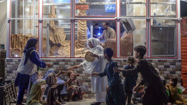 Женщина раздает хлеб нуждающимся детям перед пекарней в Кабуле - Sputnik International