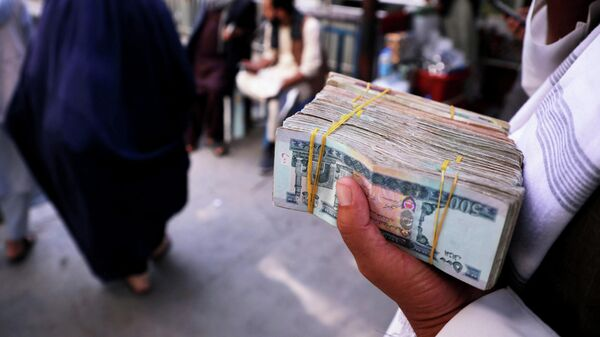 A person holds a bundle of Afghan afghani banknotes at a money exchange market, following banks and markets reopening after the Taliban took over in Kabul, Afghanistan, September 4, 2021.  - Sputnik International