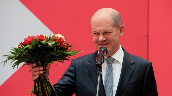 Social Democratic Party (SPD) leader and top candidate for chancellor Olaf Scholz receives flowers, one day after the general elections in Berlin, Germany, September 27, 2021 - Sputnik International