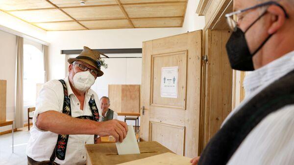 Мужчина в традиционном баварском костюме голосует в Бенедиктбойерне, Германия - Sputnik International
