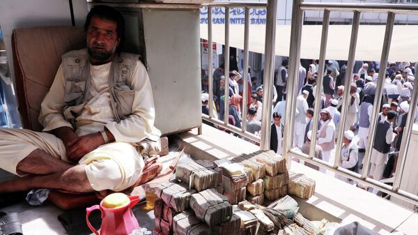 An Afghan money exchange dealer waits for customers at a money exchange market, following banks and markets reopening after the Taliban took over in Kabul, Afghanistan, September 4, 2021 - Sputnik International