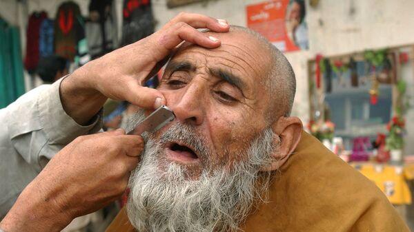 Уличный парикмахер бреет клиента в Джелалабаде, 2006 год - Sputnik International