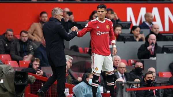 Manchester United's Norwegian manager Ole Gunnar Solskjaer (L) shakes hands with Manchester United's Portuguese striker Cristiano Ronaldo as he comes off the substitutes bench  during the English Premier League football match between Manchester United and Everton at Old Trafford in Manchester, north west England, on October 2, 2021. - Sputnik International
