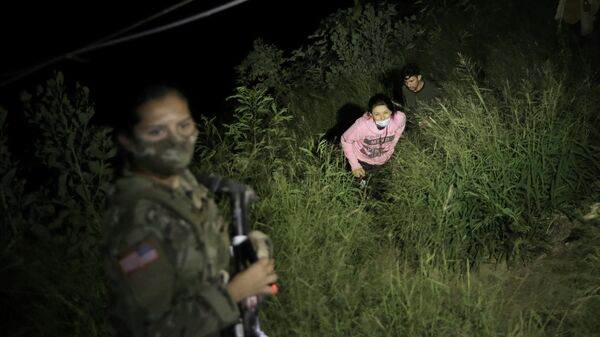 A Texas National Guard member illuminates a path as migrants cross over to the U.S., north of the Roma–Ciudad Miguel Aleman International Bridge, which spans the Rio Grande border with Mexico, in Roma, Texas, U.S. October 1, 2021. Picture taken October 1, 2021 - Sputnik International