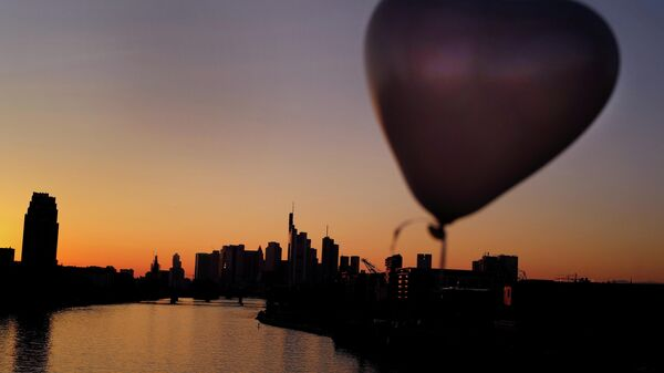 A heart-shaped balloon is seen during sunset in front of the skyline of the banking district in Frankfurt, Germany, October 10, 2021. - Sputnik International