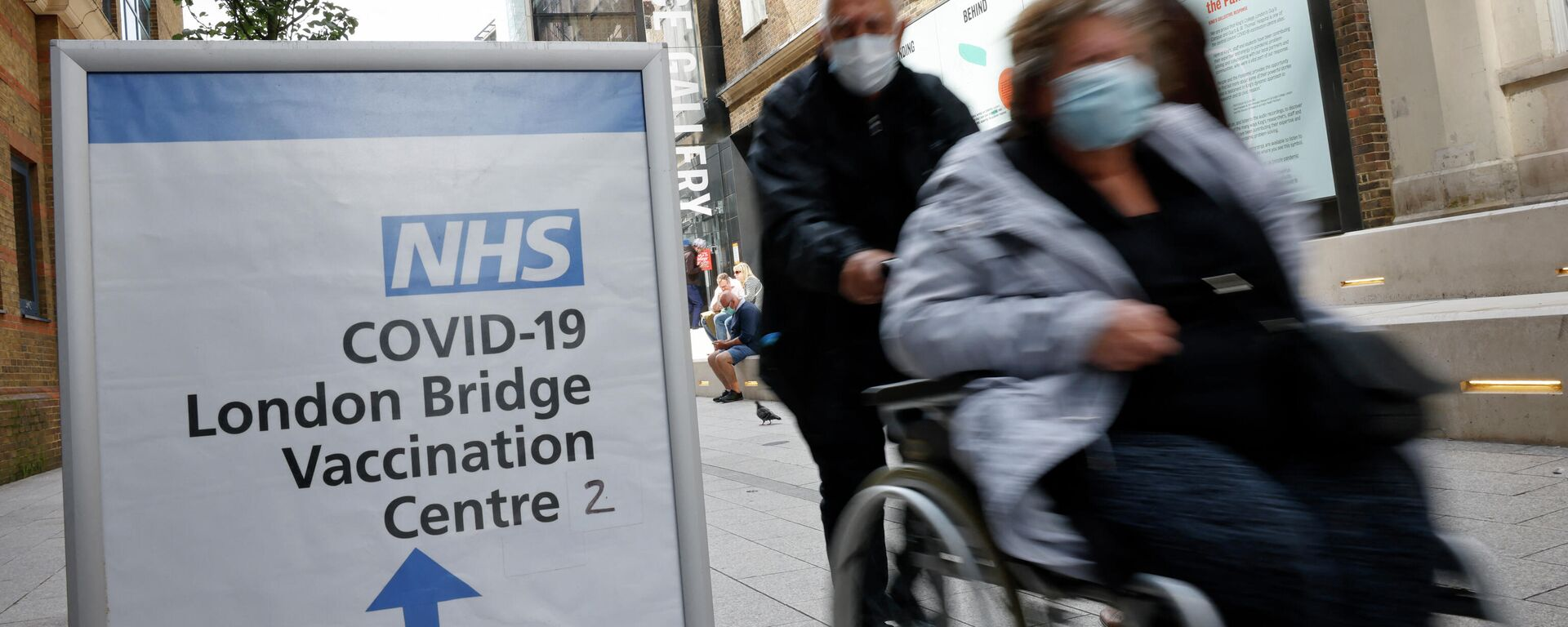 People pass signs indicating the entrance to the London Bridge Vaccination Centre in London on August 9, 2021 - Sputnik International, 1920, 12.10.2021