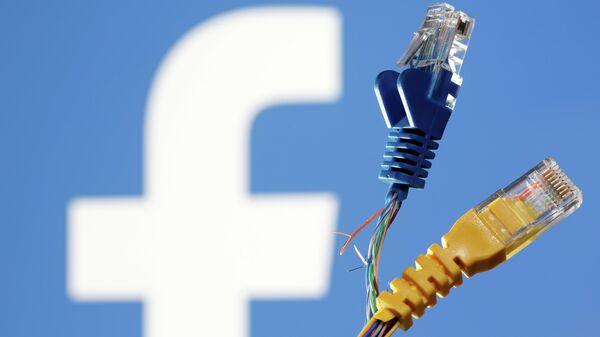 Broken Ethernet cables are seen in front of displayed Facebook logo in this illustration taken October 5, 2021 - Sputnik International