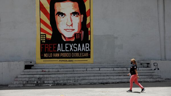A woman walks by a mural in support of the liberation of businessman Alex Saab, who was detained in Cape Verde on charges of laundering money for the government of Venezuelan President Nicolas Maduro, in Caracas - Sputnik International