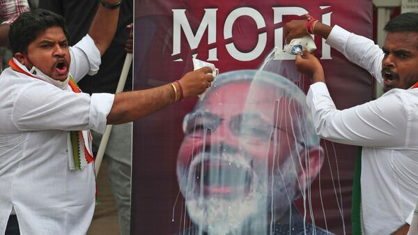 FILE - In this Friday, June 11, 2021 file photo, activists of India's opposition Congress party pour milk over a poster of Indian Prime Minister Narendra Modi, to mockingly celebrate fuel price reaching the century mark, during a protest against the hike of petrol and diesel price in Hyderabad, India.  - Sputnik International