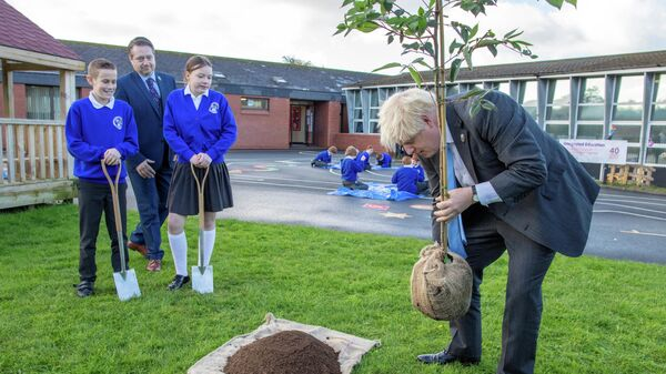 Britain's Prime Minister Boris Johnson plants a tree during a visit to Crumlin Integrated Primary School in County Antrim - Sputnik International