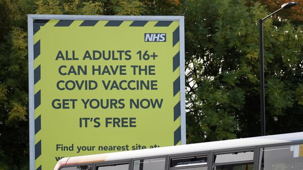 People on a bus pass a sign encouraging the public to get their COVID-19 vaccine doses in Manchester - Sputnik International