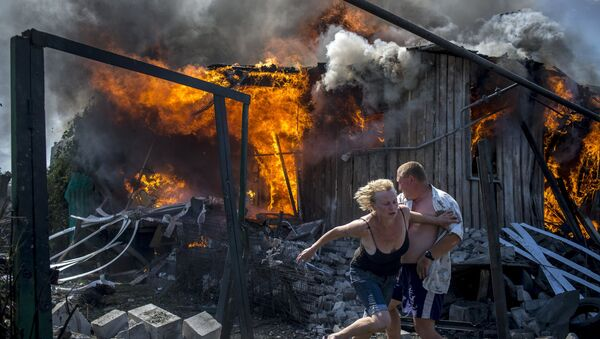 Local residents flee from a burning home hit by an air strike by the Ukrainian armed forces in Lugansk. - Sputnik International