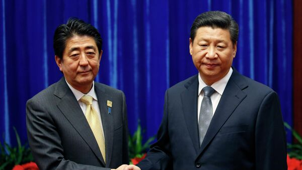 Japan's Prime Minister Shinzo Abe, left, and China's President Xi Jinping, right, shake hands during their meeting at the Great Hall of the People, on the sidelines of the Asia-Pacific Economic Cooperation (APEC) summit, in Beijing, Monday, Nov. 10, 2014. An uneasy handshake Monday between Xi and Abe marked the first meeting between the two men since either took power, and an awkward first gesture toward easing two years of high tensions. - Sputnik International