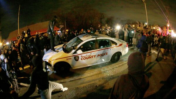 A protester squirts lighter fluid on a police car as the car windows are shuttered near the Ferguson Police Department - Sputnik International