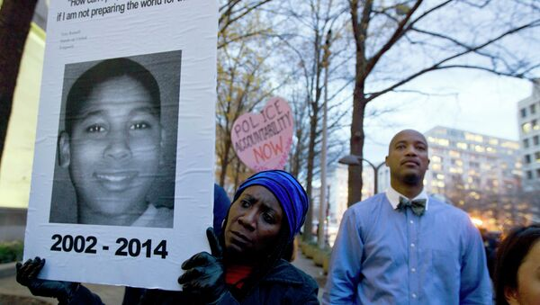 A protester holds a picture of Tamir Rice, the boy fatally shot by a rookie police officer, during a protest in response to a grand jury's decision in Ferguson to not indict police officer Darren Wilson. Protesters across the U.S. have walked off their jobs or away from classes in support of the Ferguson protesters. Rice's death has also sparked community demonstrations against police shootings. - Sputnik International