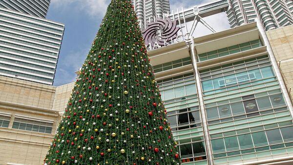 People walk around a giant Christmas tree on display against the Malaysia's landmark Petronas Twin Towers in Kuala Lumpur, Malaysia, Dec. 6, 2014 - Sputnik International