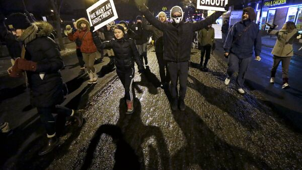 Protesters march during a rally near the Chicago Police headquarters after the announcement of the grand jury decision not to indict police officer Darren Wilson in the fatal shooting of Michael Brown, an unarmed black 18-year old, Monday, Nov. 24, 2014, in Chicago. - Sputnik International