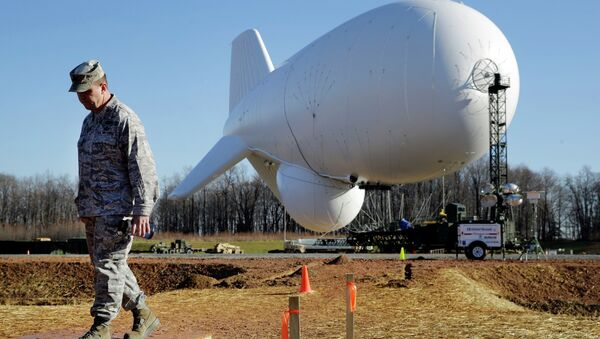 NORAD's Air Force Col. Chuck Douglass walks in front of an unmanned aerostat that is part of a new U.S. military cruise-missile defense system during a media preview, Wednesday, Dec. 17, 2014, in Middle River, Md. Military officials said a pair of helium-filled aerostats stationed in Maryland are intended provide early detection of cruise missiles over a large swath of the East Coast, from Norfolk, Va., to upstate New York, during a three-year test. JLENS, short for Joint Land Attack Cruise Missile Defense Elevated Netted Sensor System, will be fully implemented this winter. - Sputnik International