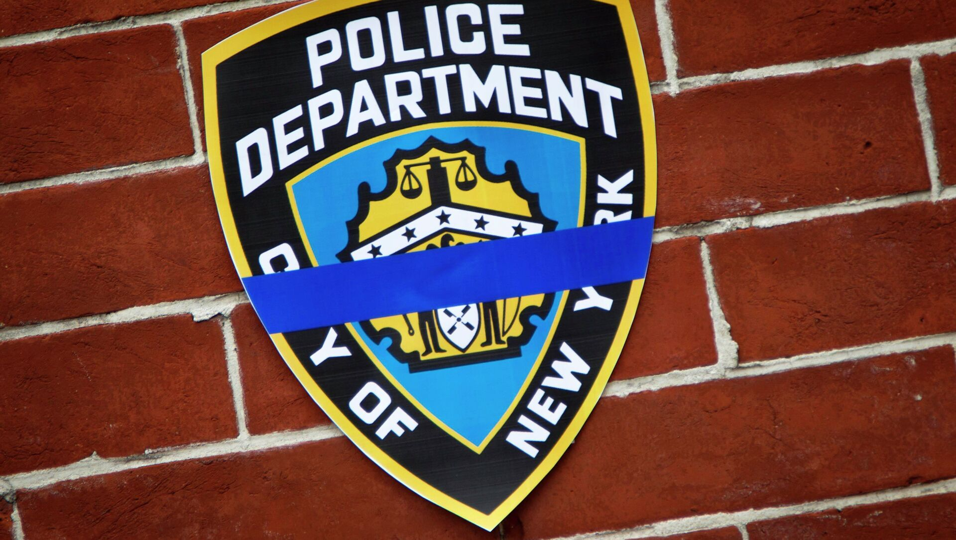 An NYPD logo is pictured on wall above makeshift memorial at the site where two police officers were shot in the head in the Brooklyn borough of New York, December 22, 2014. - Sputnik International, 1920, 04.08.2021