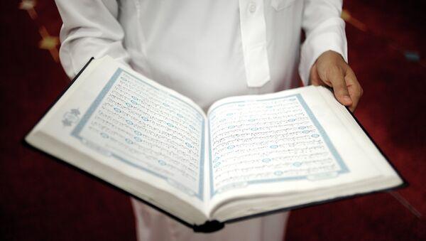 An imam holds the Quran after a prayer at a mosque - Sputnik International
