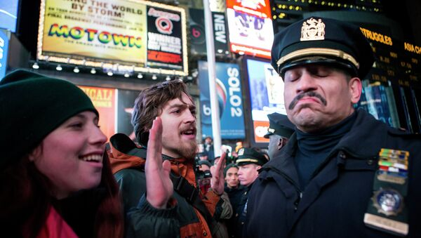 A NYPD policeman (R) reacts next to people protesting against the Staten Island death of Eric Garner during an arrest in July, at midtown Manhattan in New York December 3, 2014 - Sputnik International