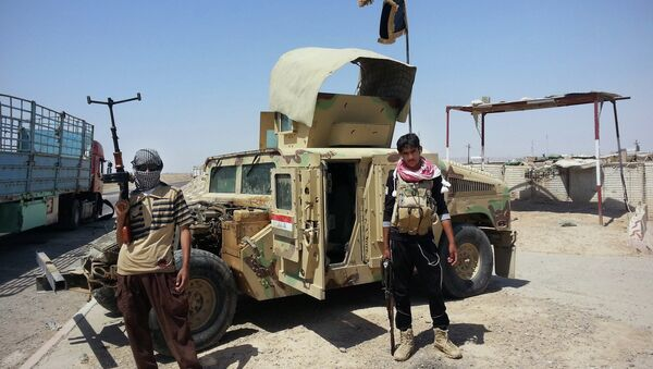 In this file photo, Islamic State group militants stand with a captured Iraqi army Humvee at a checkpoint outside Beiji refinery, around 155 miles north of Baghdad, Iraq. - Sputnik International