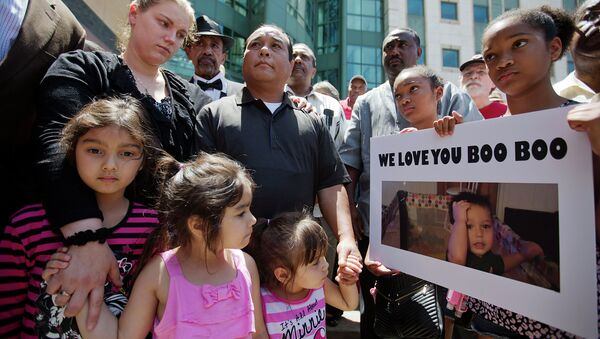 Alecia and Boun Khan Phonesavanh, from rear left, the parents of 19-month-old Bounkham Phonesavanh who was severely burned by a flash grenade during a SWAT drug raid, attend a vigil with their daughters outside Grady Memorial Hospital where he is undergoing treatment, Monday, June 2, 2014, in Atlanta. - Sputnik International