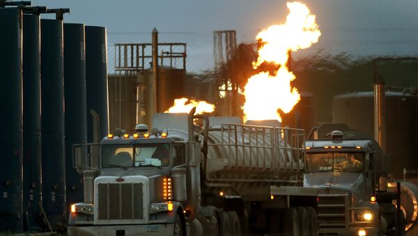 Drivers and their tanker trucks, capable of hauling water and fracking liquid line up near a natural gas burn off flame and storage tanks in Williston, N.D. - Sputnik International