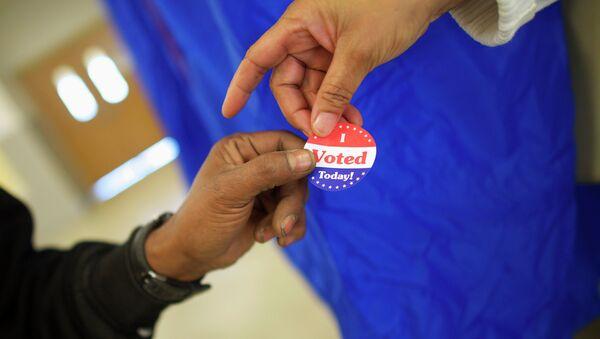Voting machine operator Robin Coffee-Ruff hands a sticker to a voter who cast his ballot at West Philadelphia High School on U.S. midterm election day morning in Philadelphia, Pennsylvania, November 4, 201 - Sputnik International