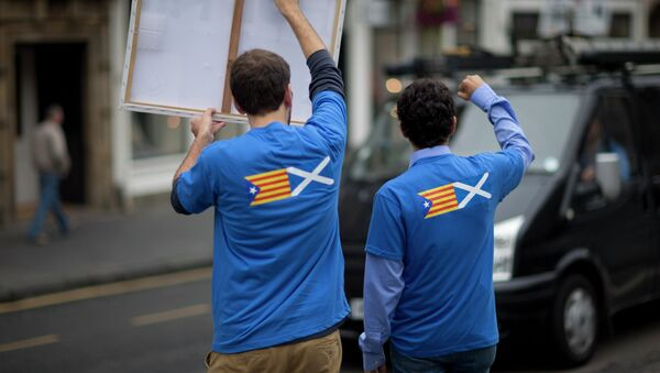 David Aguilar, left, and Aleix Sarri from Catalonia, who are visiting Scotland to support the Scottish independence referendum, gesture and hold up a placard supporting a Yes vote at passing motorists in Edinburgh, Scotland, Thursday, Sept. 18, 2014 - Sputnik International