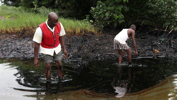 In this June 20, 2010 file photo, men walk in an oil slick covering a creek near Bodo City in the oil-rich Niger Delta region of Nigeria - Sputnik International