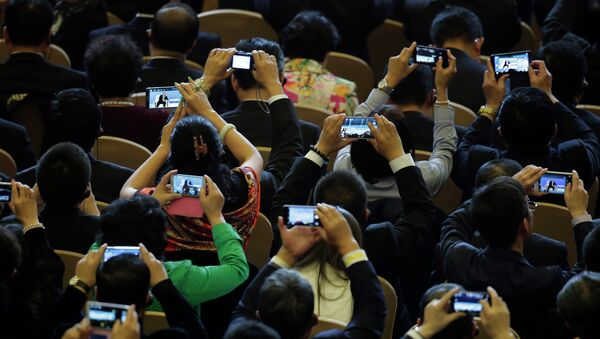 Delegates use their smartphones to take pictures of Russian President Vladimir Putin speaks during a dialogue session with delegates during the APEC CEO Summit - Sputnik International