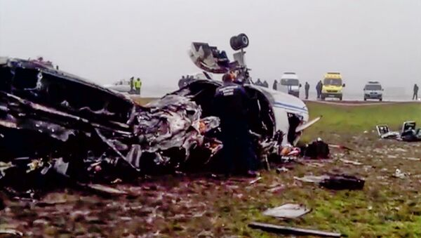 In this image made from video provided by Russian State Television Rossiya, investigators works at the wreckage of a private jet which collided with a snowplow at Vnukovo airport in Moscow, Tuesday, Oct. 21, 2014 - Sputnik International