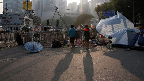 Pro-democracy protesters stand at an occupied area before barricades are removed outside government headquarters in Hong Kong's Admiralty district Tuesday, Nov. 18, 2014. - Sputnik International