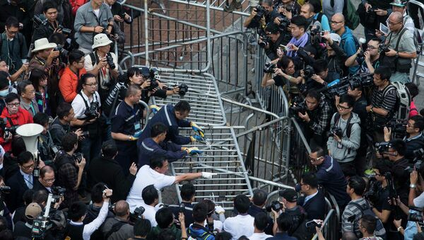 Building employees dismantle a barricade outside Citic Tower in accordance with a court injunction to clear up part of the protest site, outside the government headquarters in Hong Kong November 18, 2014. - Sputnik International
