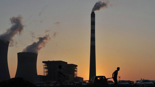 A worker pulls a cart in front of the smoking chimneys of a power plant in Hefei - Sputnik International