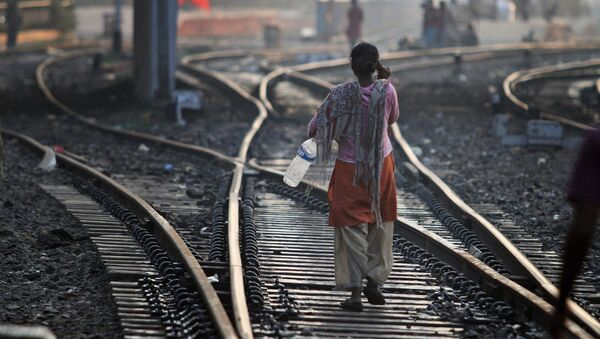 An Indian woman walks after defecating on a railway track, on World Toilet Day in Gauhati, India, Wednesday, Nov. 19 2014 - Sputnik International