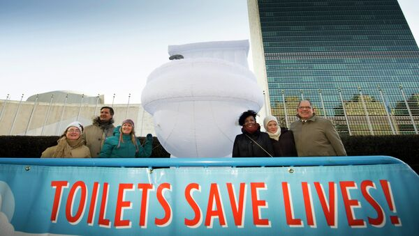 """In this photo provided by the United Nations, a small group of UN staff, with a """"Toilets Save Lives!"""" banner, poses for a photo with a 15-foor-high inflatable toilet, in front of United Nations headquarters, in observance of """"World Toilet Day,"""" Wednesday, Nov. 19, 2014 - Sputnik International"""