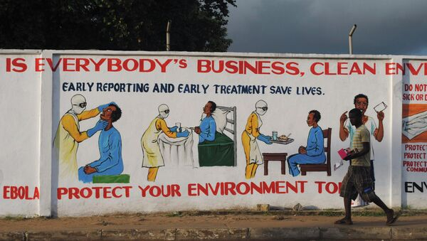 A man walks by a mural with health instructions on treating the Ebola virus, in Monrovia, November 18, 2014 - Sputnik International