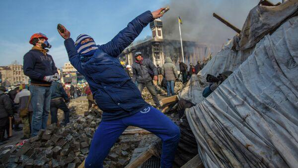 A protester throws stone on Maidan square in Kiev, Ukraine, Feb 19, 2014 - Sputnik International