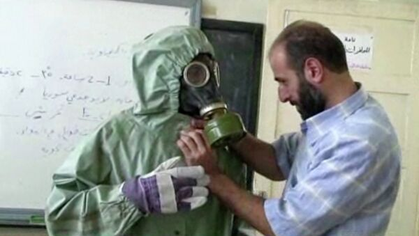 Volunteer adjusting a gas mask and protective suit on a student during a classroom session a on how to respond to a chemical weapons attack in Aleppo, Syria - Sputnik International