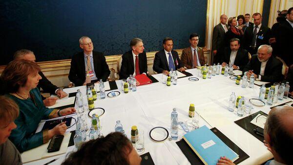 EU envoy Catherine Ashton (L), Britain's Foreign Secretary Philip Hammond (C) and Iranian Foreign Minister Javad Zarif sit at a table during talks in Vienna November 21, 2014 - Sputnik International