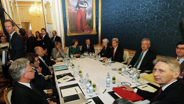 French Foreign Minister Laurent Fabius, sitting third left, former EU foreign policy chief Catherine Ashton, rear center, U.S. Secretary of State John Kerry, fourth right, and British Foreign Secretary Philip Hammond wait for the start of closed-door nuclear talks on Iran in Vienna, Austria, Friday, Nov. 21, 2014 - Sputnik International